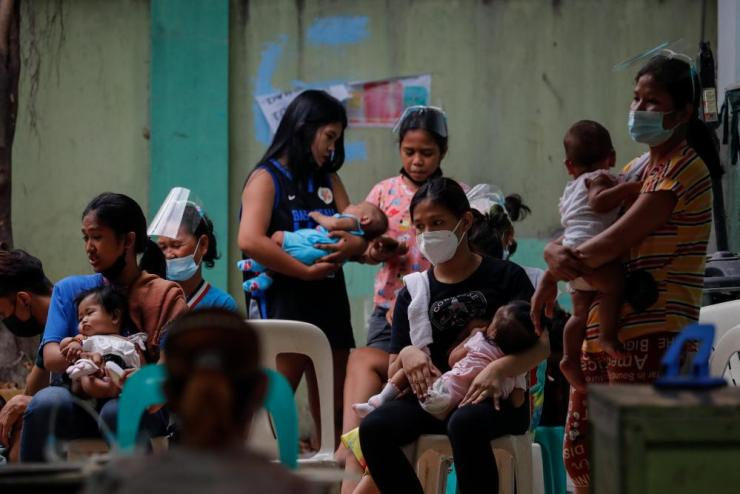 Mothers carry their babies as they lineup for checkup at a public health center in Manila, Philippines, on 27 April 2021. The Philippines on 26 April surpassed one million Covid-19 cases, making it the second highest in South East Asia after Indonesia, despite the country's lockdown.