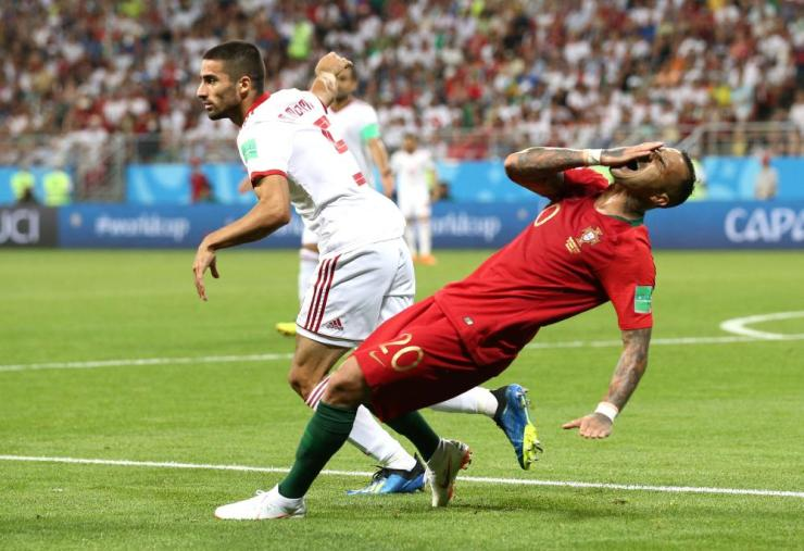 Ricardo Quaresma of Portugal falls down after a minimal contact with Milad Mohammadi.