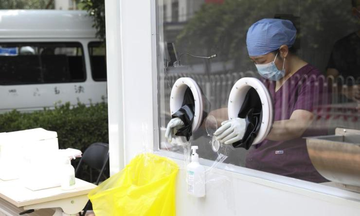Medical workers prepare to work at nucleic acid testing kiosks on 25 June 2020 in Beijing, China.