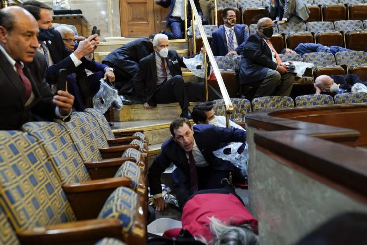 People shelter in the House gallery as protesters try to break into the House Chamber.