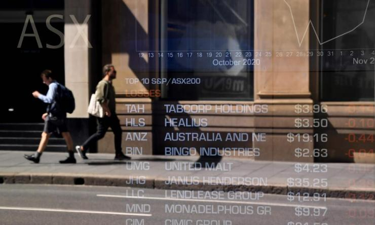 Pedestrians are reflected in a window of the Australian Securities Exchange (ASX) in Sydney on November 9, 2020.