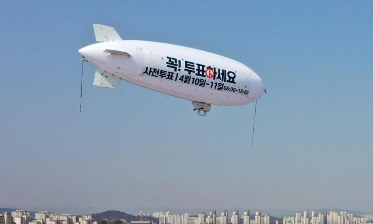 A blimp with a sign calling for people to participate in early voting flies above Gwangju, South Korea, 9 April 2020.