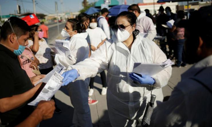 Personnel from an assembly factory hand out job application forms to job seekers in Ciudad Juarez, Mexico 17 June 2020.