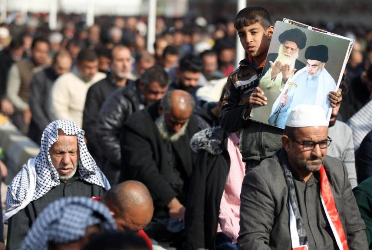 A young boy holds a poster showing top Shiite cleric Grand Ayatollah Ali Sistan (L) and Shiite cleric Moqtada al-Sadr (R) as the supporters of the latter take part in Friday prayers in the Sadr City suburb of the capital Baghdad, on January 3, 2020, the day after the US assassinated Iranian general Qassem Suleimani just a few miles away near the airport