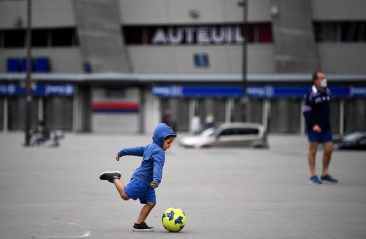 A child plays football in front of the Parc des Princes' Auteuil tribune entrance in Paris. Younger children are due back to school on 12 May