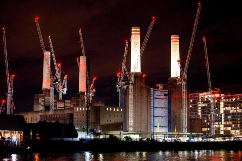 Two of Battersea Power Station's chimneys are lit up for the first time since they were rebuilt, November 2017. Carillion is working on the redevelopment.