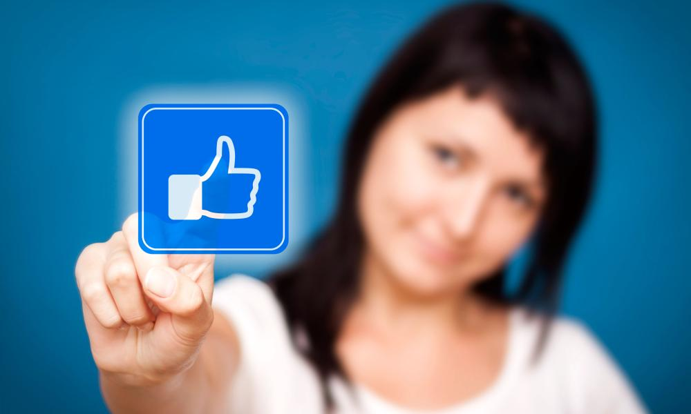 Woman is touching the Facebook like button.