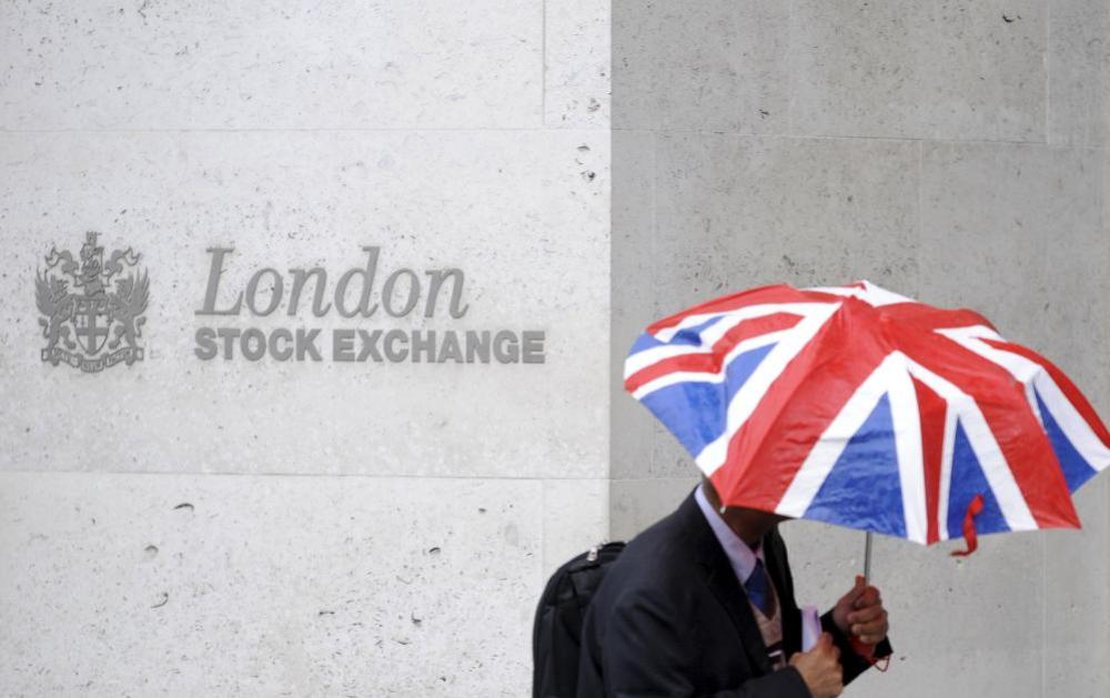 A worker sheltering from the rain as he passes the London Stock Exchange in the City of London.