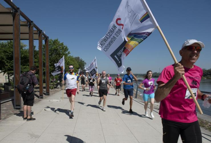 Participants of the Equality Jog hold rainbow flags while running on 19 June, 2021 in Warsaw, Poland.
