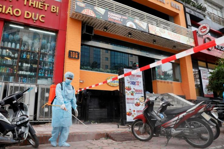 A worker sprays disinfectant next to a restaurant where a worker tested positive with Covid-19 after travel from Da Nang, in Hanoi, Vietnam.