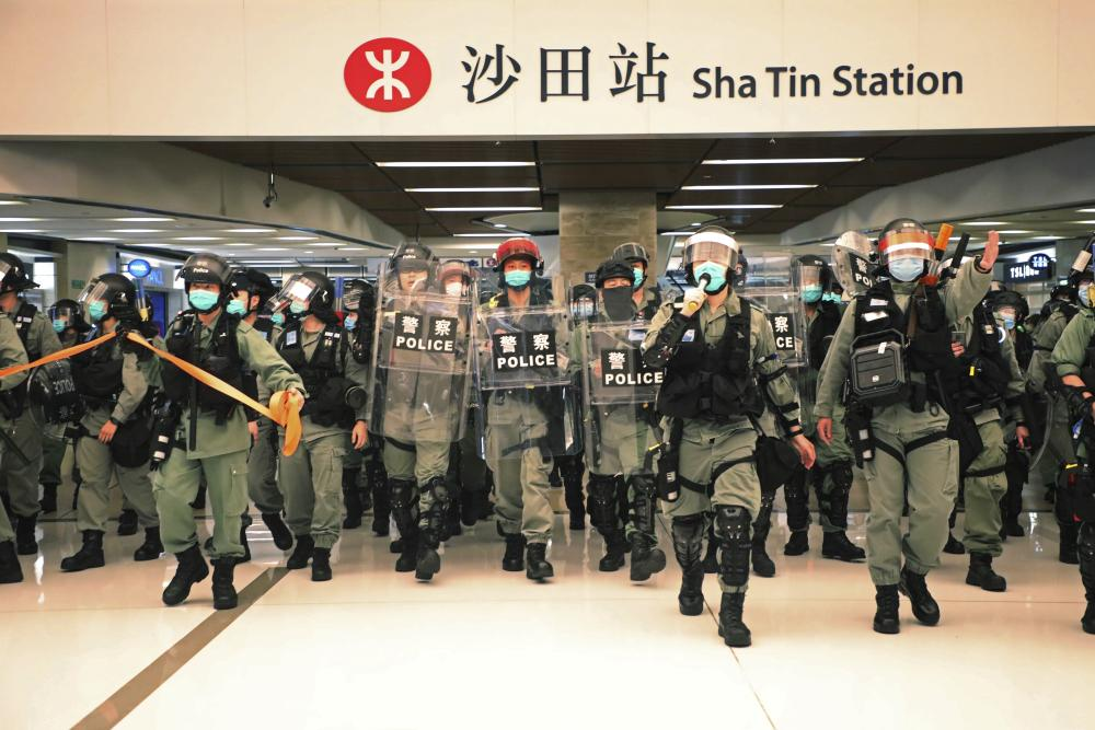 Riot police enter a shopping mall to disperse May Day protesters in Hong Kong