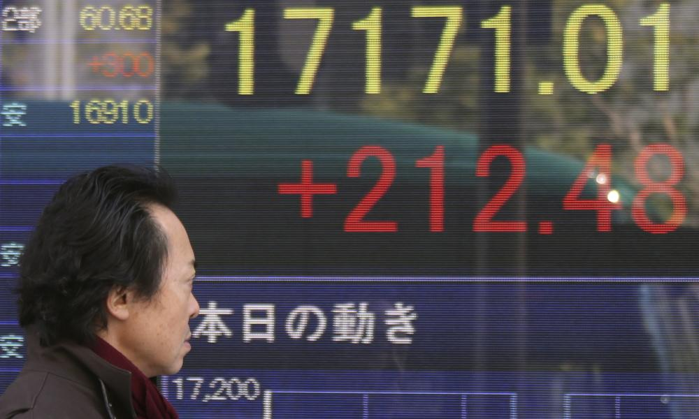 A man walks by an electronic stock board of a securities firm in Tokyo earlier today