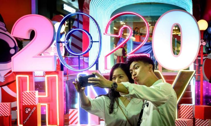 A young couple takes a selfie picture in front of a sign reading '2020 HNY' in downtown Bangkok on December 27, 2019.