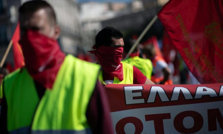 "Members of the communist-affiliated trade union PAME wear scarves reading ""The covered mouths have a voice"" during a rally commemorating May Day, following the coronavirus disease (COVID-19) outbreak, in Athens, Greece, May 1, 2020."