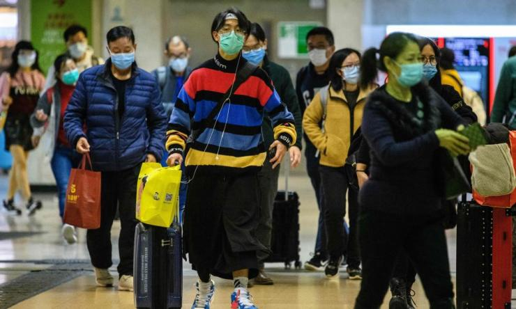 Passengers protective wear face masks as they arrive from Shenzhen to Hong Kong at Lo Wu MTR station, hours before the closing of the Lo Wu border crossing in Hong Kong on Monday.