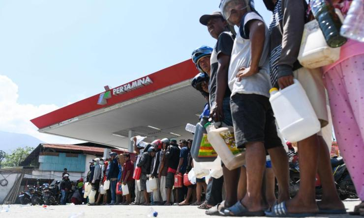 Survivors line up at a service station to get gasoline in Palu