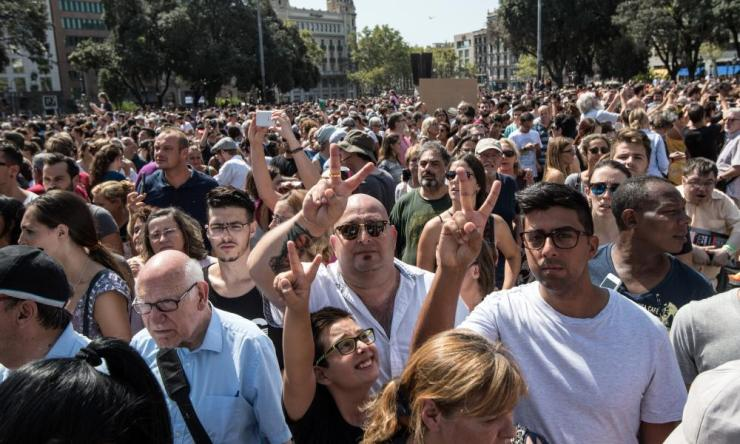 People gesture as they leave Plaça de Catalunya after the vigil