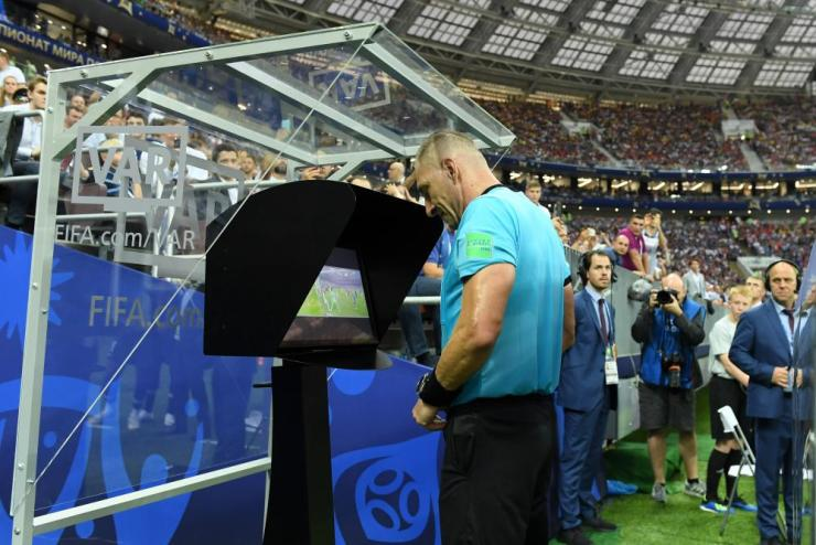 Referee Nestor Pinata consults VAR before awarding France a penalty.