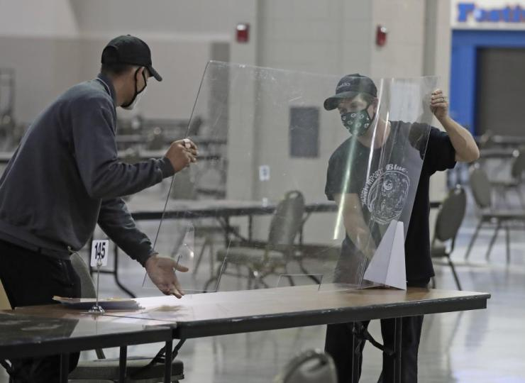 Workers place protective plastic sheets on tables in preparation for a recount of ballots in Milwaukee.