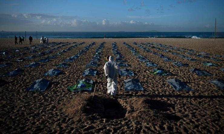 A demonstrator from the Rio de Paz human rights activist group digs a symbolic grave in front of rows of bags symbolizing bodybags on Copacabana beach, during a protest against the Brazilian governments handling of the coronavirus pandemic, in Rio de Janeiro on April 30, 2021.