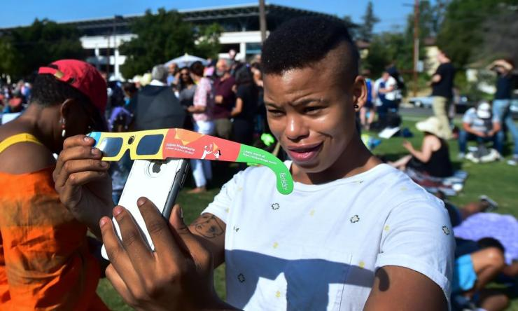 Asha Moore uses solar eclipse glasses and her iphone to show a friend from Canada on the phone the view of the partial solar eclipse from Beckman Lawn at Caltech in Pasadena, California.