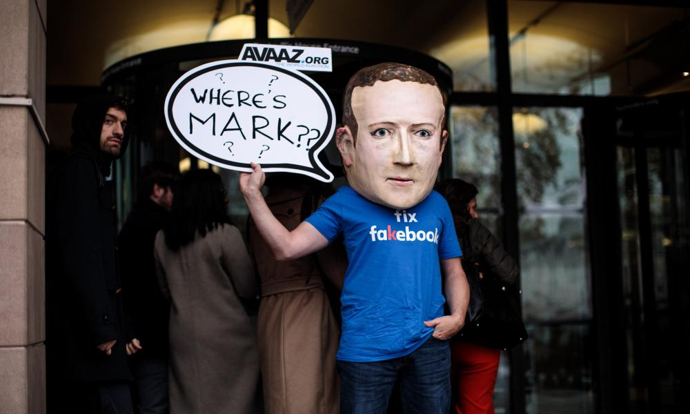 A protester wearing a papier-mache Mark Zuckerberg head outside Portcullis House in November 2018.