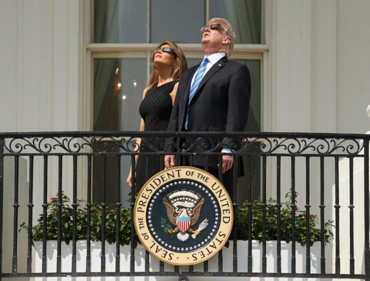 President Donald Trump and first lady Melania Trump wear protective glasses as they view the solar eclipse, Monday at the White House in Washington.