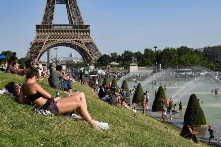 People sunbathe and cool off at the Trocadero Fountains next to the Eiffel Tower in Paris on Tuesday.