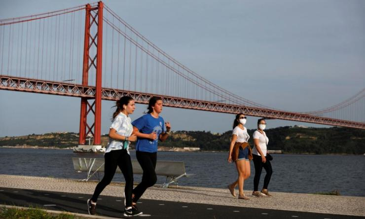 People walk past 25th April Bridge along the Tagus river, in Lisbon, Portugal, May 3, 2020. REUTERS/Rafael Marchante
