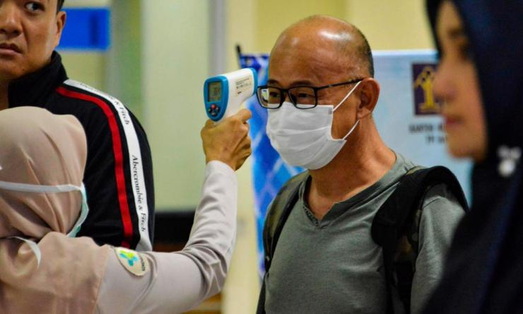 An Indonesian health official checks the temperature of a passenger wearing a face mask upon his arrival at the Sultan Iskandar Muda International Airport in Blang Bintang.