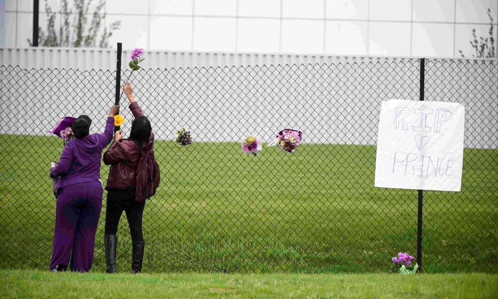 Prince fan Mona Shelton an unidentified employee place flowers outside of Paisley Park in