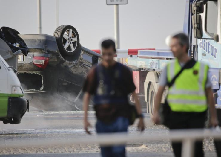 Police officers walk near an overturned car onto a platform at the spot where terrorists were intercepted by police in Cambrils, Spain, Friday, Aug. 18, 2017. The police force for Spain's Catalonia region says the five suspects shot and killed in the resort town of Cambrils were carrying bomb belts, which have been detonated by the force's bomb squad. (AP Photo/Emilio Morenatti)