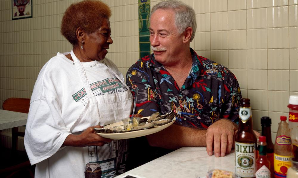 New Orleans writer and television personality Ronnie Virgets is served the house specialty, ice-cold oysters on the half shell, by Alma Griffin at Casamento Seafood Restaurant in Uptown New Orleans, Louisiana