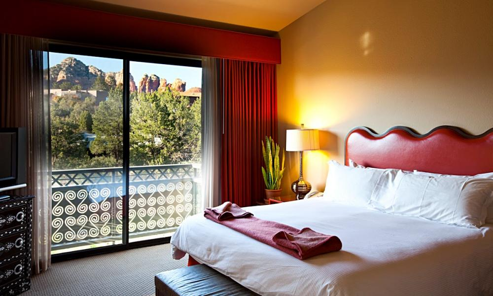 A bedroom with a view of the mountains at Sedona Rouge hotel, Sedona, Arizona, US.