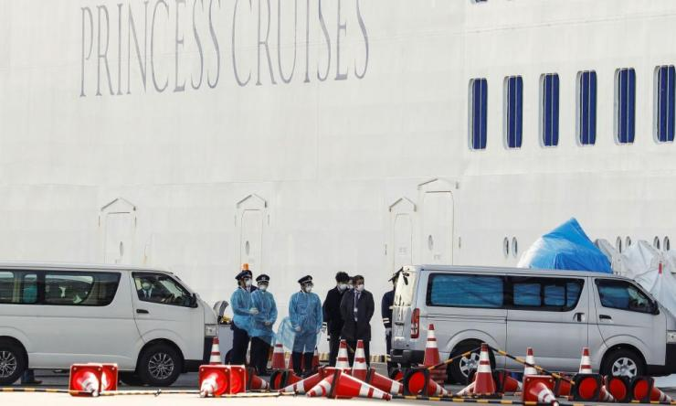Workers wearing protective gear prepare to transfer passengers, who tested positive for coronavirus, from the cruise ship Diamond Princess to a hospital.