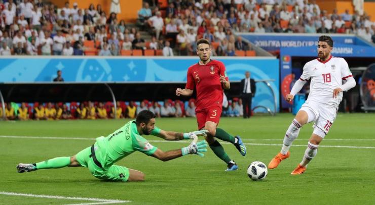 Portugal's Rui Patricio dives for the ball ahead of Alireza Jahanbakhsh.
