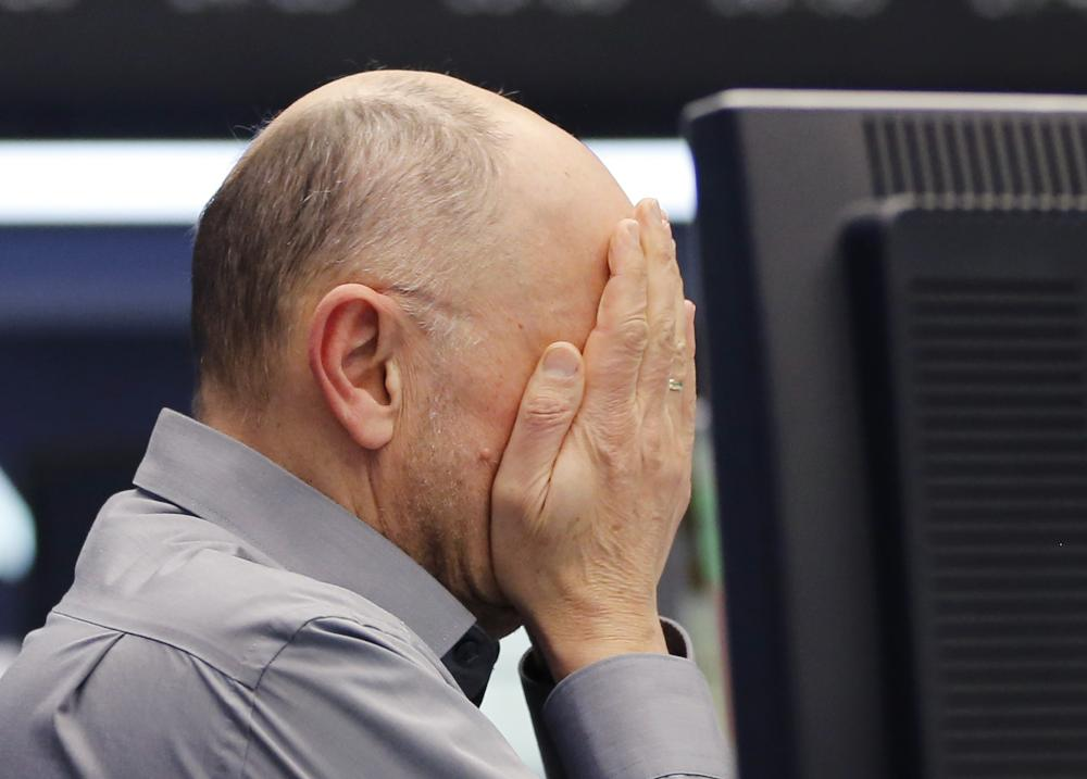 A trader wipes his face at the stock market in Frankfurt today.