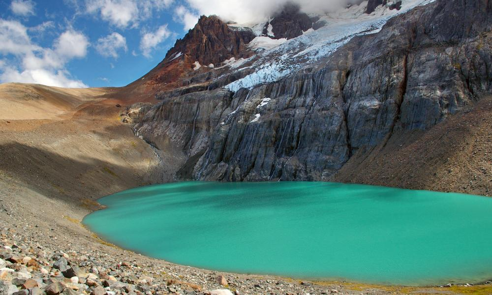 A beautiful turquoise glacier lake at the top of Cerro Castillo mountain. Blue sky with clouds.
