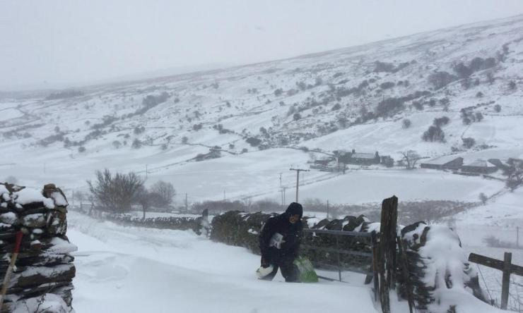Man struggling through the snow with shopping