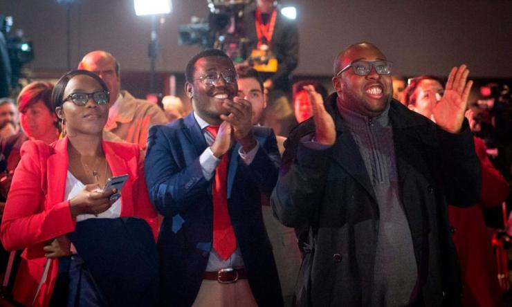 Supporters of Liberal party candidate, Justin Trudeau, celebrate after the first results are announced at the Palais des Congres in Montreal.