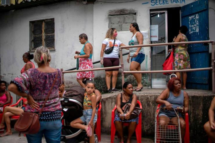 People wait to get donations of basic food supplies distributed by an NGO at the Cidade de Deus (City of God) favela in Rio de Janeiro