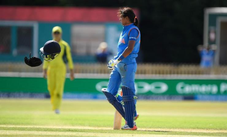 Harmanpreet Kaur reacts by throwing her helmet off onto the ground after reaching her century.