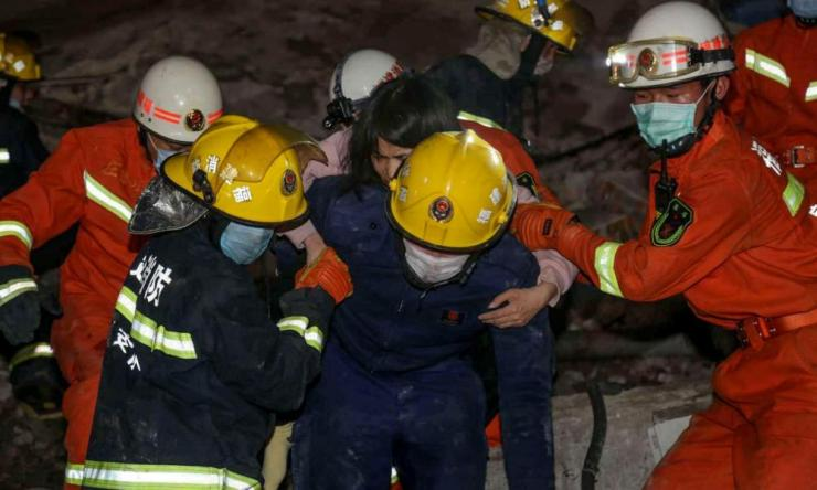 A woman is rescued from the rubble of a collapsed hotel in Quanzhou, in China's eastern Fujian province on 7 March.