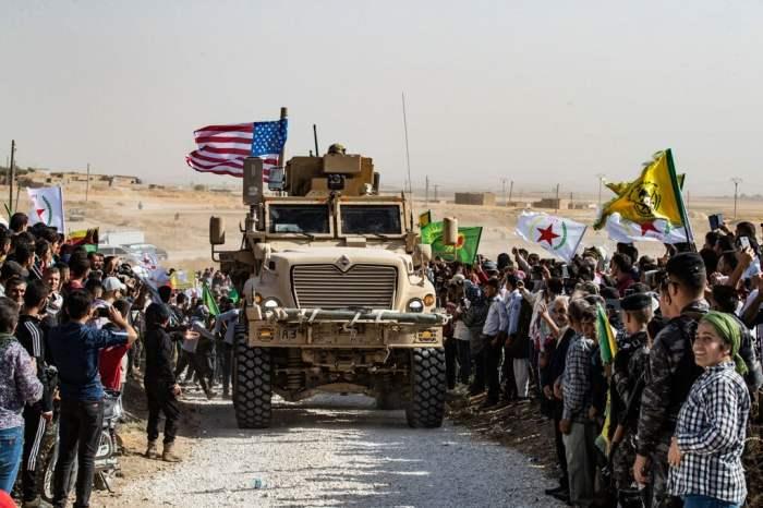 Curdi siriani intorno a un veicolo dell'esercito statunitense durante una manifestazione contro le minacce di attacchi da parte della Turchia. Periferia di Ras al Ain, nella provincia siriana di Hasakeh, vicino al confine turco, il 6 ottobre 2019. - Delil Souleiman, Afp