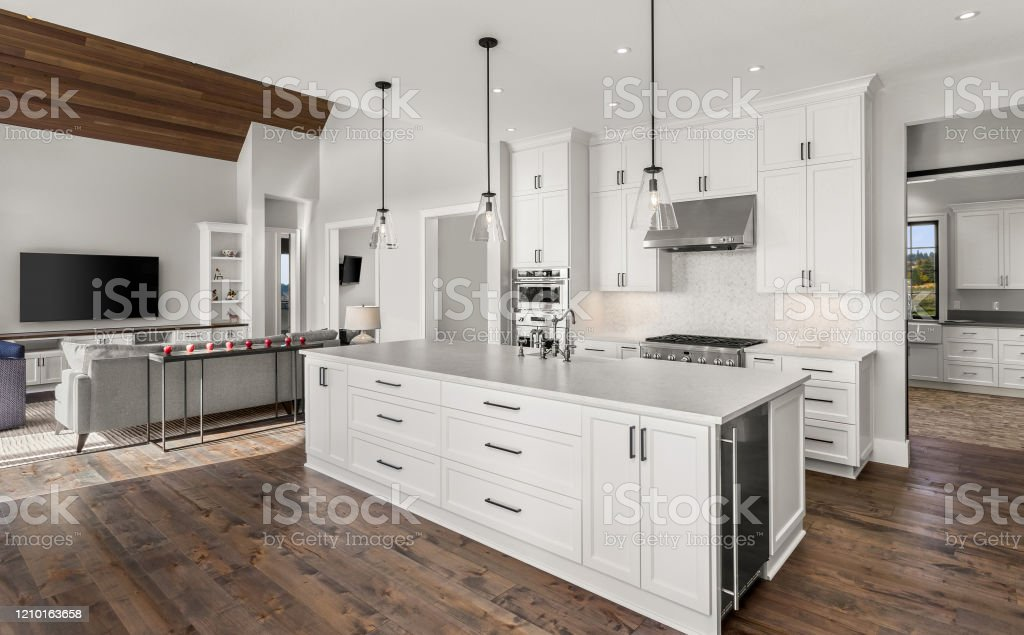 beautiful kitchen in new luxury home with island pendant lights and hardwood floors features view of living room with vaulted ceiling stock photo download image now istock