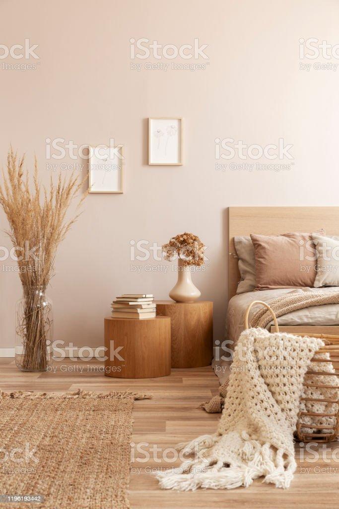 https www istockphoto com fr photo chambre beige denfant avec la table de nuit en bois avec des fleurs et le lit simple gm1196193442 341142905