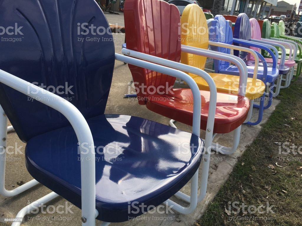 https www istockphoto com photo blue red yellow retro chair in the foreground colorful patio chairs gm894599028 247312952