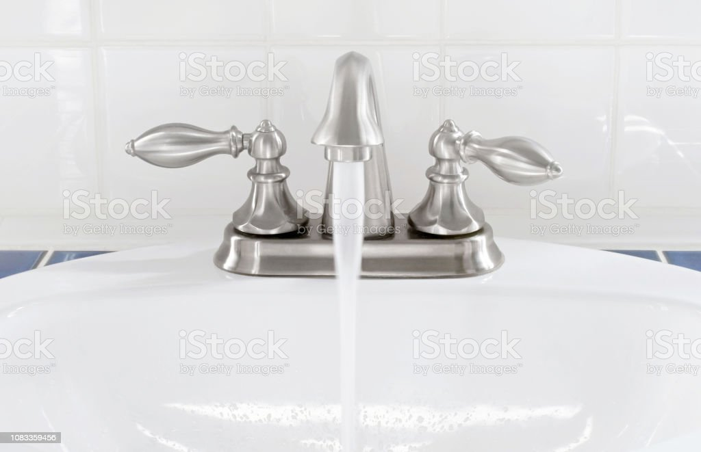 brushed nickel faucet with running water stock photo download image now istock