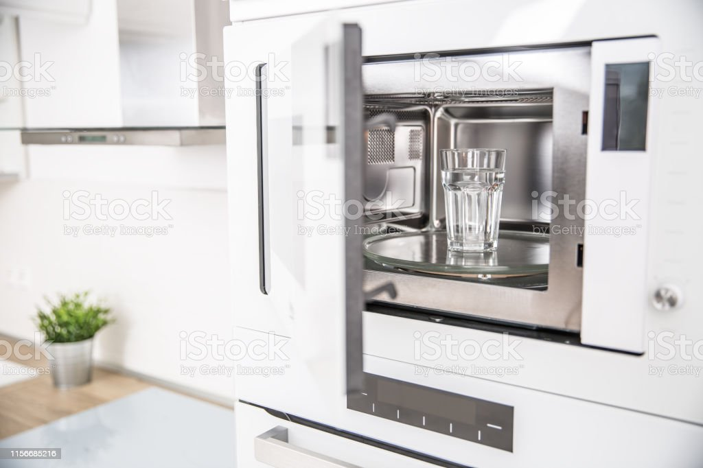 builtin microwave oven in the kitchen with a cup of pure water stock photo download image now istock