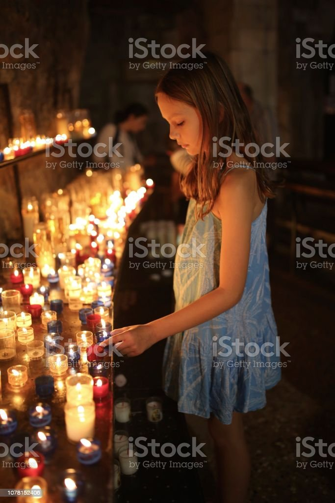 child lighting candle in a church stock photo download image now istock
